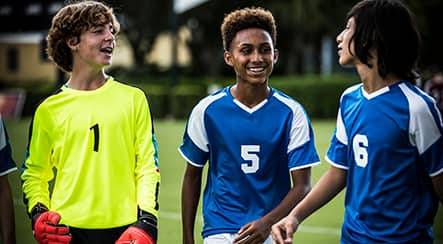 A goalie and 2 other boy soccer players talking and laughing