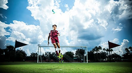 A boy soccer player jumping to head a ball