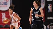 A female basketball player runs down court dribbling a basketball alongside an opponent at the Junior NBA World Championship event