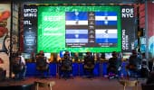 A row of competitors sit at desks in front of individual monitors and a large scoreboard