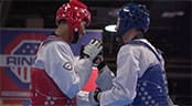 Two men wearing martial arts uniforms, including helmets and body pads, shake hands