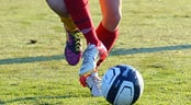 A soccer ball flies off the foot of a player while an opponent's foot tries to stop it