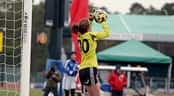 A female goal keeper stops a shot on goal during a soccer match