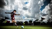 Male youth soccer player kicking  a soccer ball towards a goal
