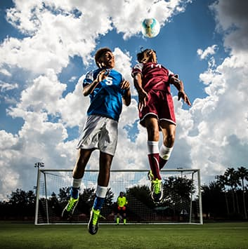 Two soccer players jumping to gain control of a soccer ball with blue sky and goal in the background.