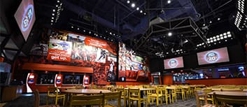 Tables and chairs fill the floor of a room witzh large TVs and a sports mural hanging on the walls at ESPN Wide World of Sports Grill