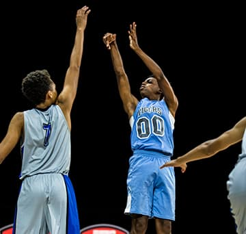 A basketball player jumps in the air following through on his shot above the outstretched arm of an opponent during a game at an ESPN Wide World of Sports venue
