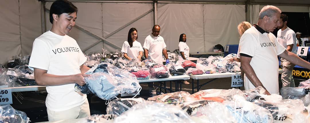 Inside one of the race tents, volunteers organize numbered tables filled with bags of each runners clothing