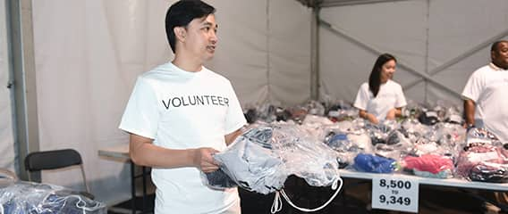 Inside a clothing tent, 3 volunteers organize numbered bags of clothes that correspond to each runner