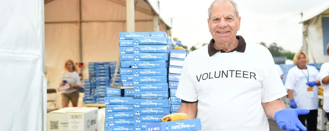Outside one of the race tents, a volunteer holds a boxed meal and one banana while standing near a table stacked with food
