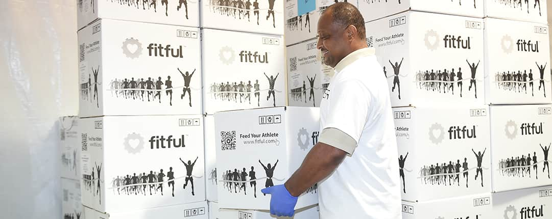 Inside one of the race tents, a volunteer takes a meal box marked Fit Ful from stacks of cases