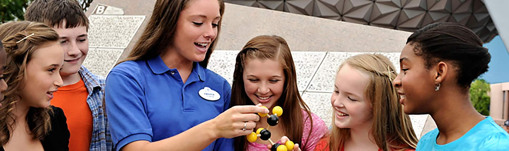 A Cast Member showing young adults a chemistry molecular model