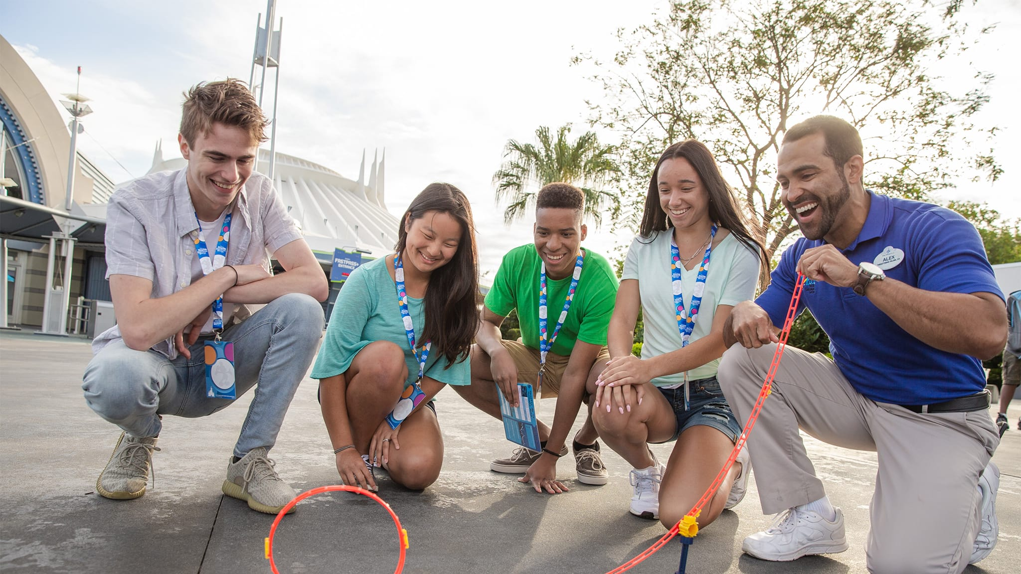 A Disney Cast Member rolls a marble down a looped plastic track as 4 teenagers observe