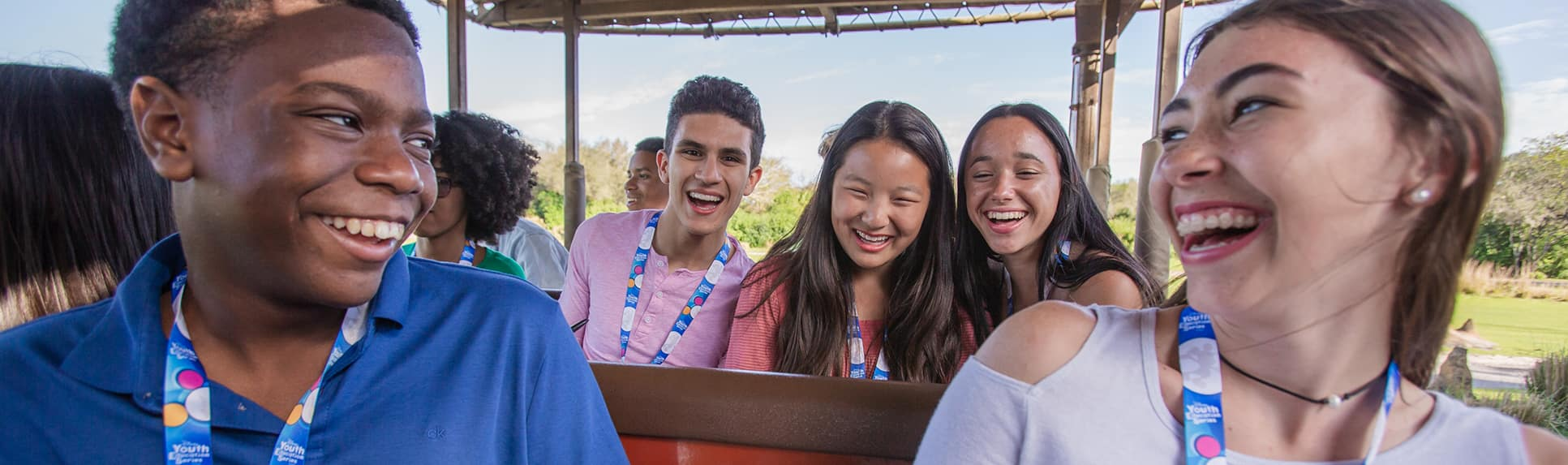 A group of teenagers in an open-air vehicle smiling at each other as they ride through a savanna