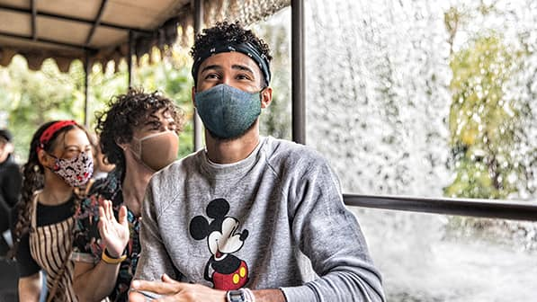 A young man wearing a bandana, a mask and a Mickey Mouse sweatshirt sits on a boat near a waterfall on the Jungle Cruise attraction at Magic Kingdom Park
