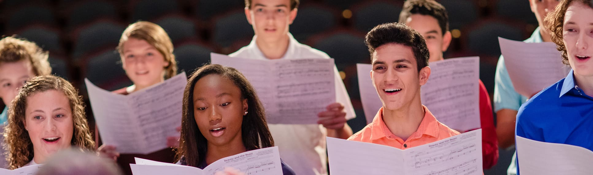 A teen choir singing as they're led by a conductor