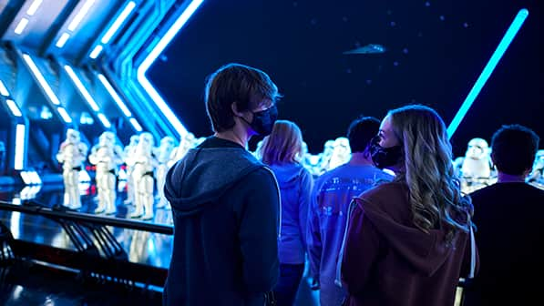 A teen boy and girl wearing masks stand at the back of a group watching Storm Troopers in Star Wars Rise of the Resistance attraction at Disney's Hollywood Studios