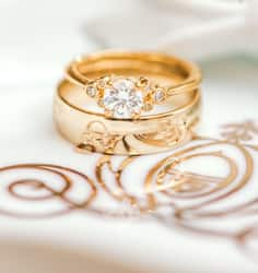 Gold wedding rings on top of a graphic of a Disney wedding carriage,